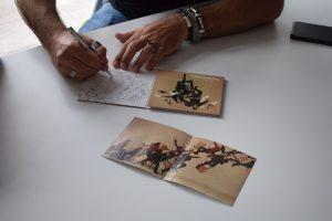 """Efecto Mariposa firmando nuestro ejemplar de """"Vuela"""". Fotografía de Tamara Ramírez"""